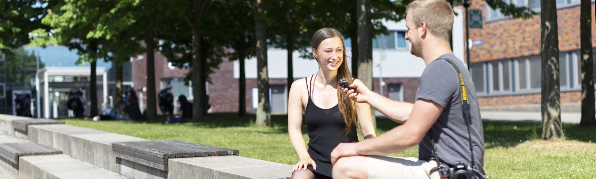 Rechts im Bild befindet sich ein junger Mann mit grauem T-Shirt, der eine Kamera um die Schulter trägt. Er hat ein Mikrofon in der Hand und hält es einer jungen Frau mit langen braunen Haaren hin, die ein schwarzes Top trägt. Es handelt sich um eine Interview-Situation. Im Hintergrund befinden sich Bäume und dahinter Gebäudefassaden. Die Personen sitzen auf einer Treppenstufe aus Stein.
