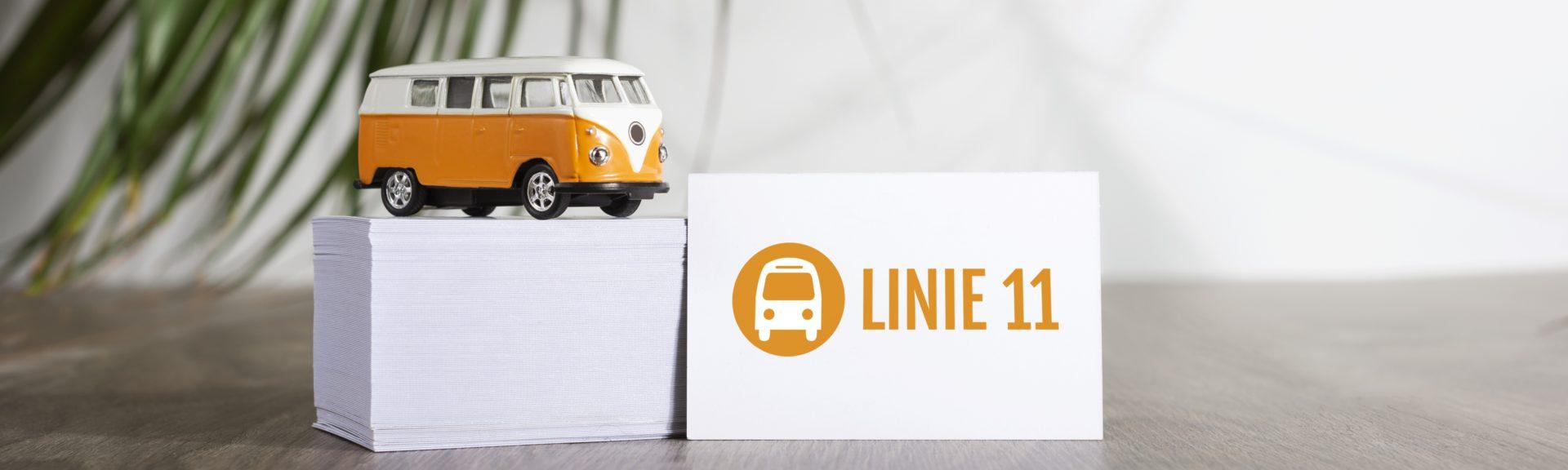 Auf einem Holztisch steht ein Stabel mit Visitenkarten. Auf dem Stapel befindet sich ein orangefarbener Spielzeug-VW-Bus mit weißem Dach. An den Stapel angelehnt steht eine einzelne Visitenkarte mit dem Logo der Linie 11.