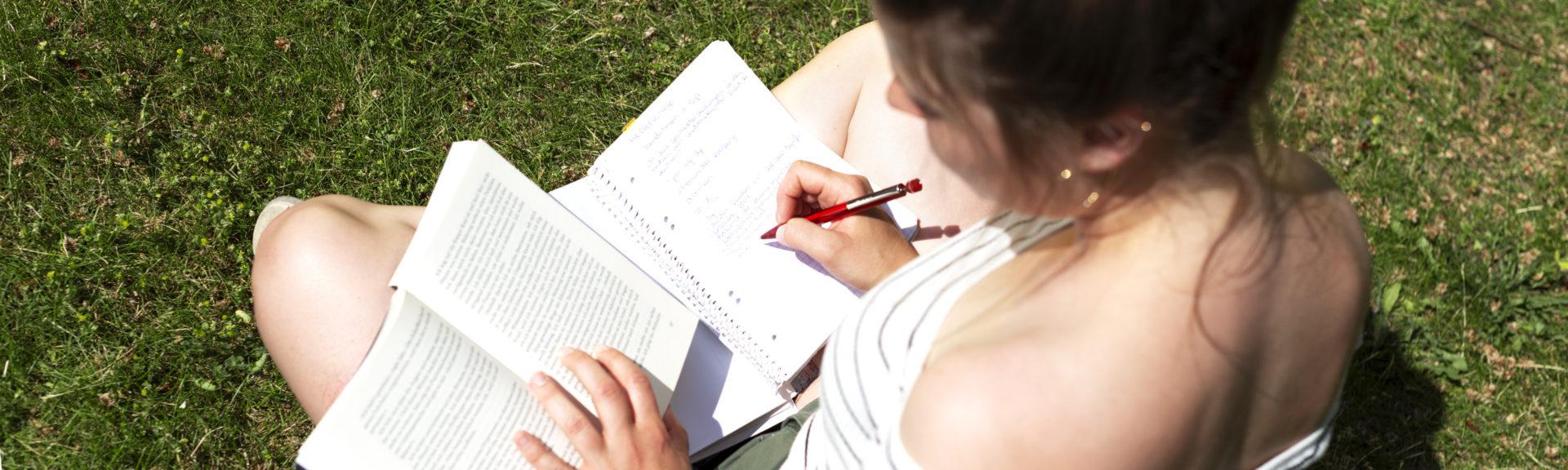 Eine junge Frau sitzt auf grünem Rasen. Auf ihren verschränkten Beinen hat sie ein offenes Buch und ein Notizheft abgelegt. In das Buch schreibt sie mit einem Kugelschreiber. Die Frau hat braune Haare und trägt ein sommerliches Shirt sowie eine kurze Hose. Wir sehen ihr schräg über die Schulter.