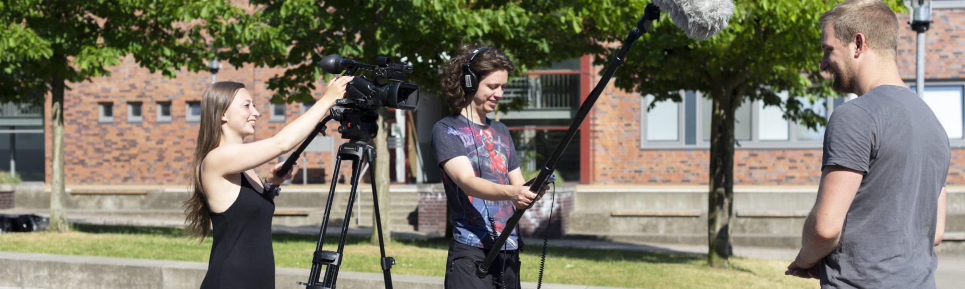 Vor einer kleinen Rasenfläche mit Bäumen steht ein Kamerateam: Es besteht aus einer jungen Frau, die eine Kamera auf einem Stativ bedient, und einem jungen Mann, der einen Kopfhörer trägt und eine Tonangel hält. Vor dem Kamerateam steht ein zweiter Mann im grauen T-Shirt. Er wird gerade interviewt.