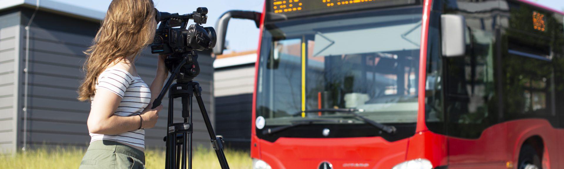 In der rechten Bildhälfte steht ein roter Bus aus dem Nahverkehr. Links steht sich eine junge Fraz mit langen braunen Haaren und sommerlicher Kleidung. Sie schaut durch den Sucher einer Kamera, die auf einem Stativ steht und zum Bus zeigt.