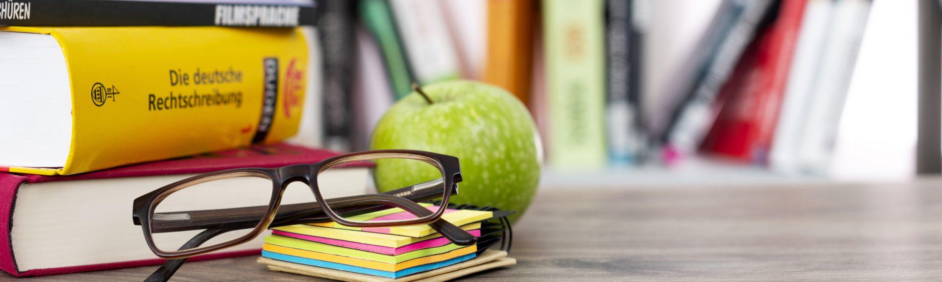 Auf einem Holztisch, der vor einem Bücherregal steht, befinden sich links drei weitere Bücher. Davor befinden sich ein Stapel Haftnotizzettel, eine zusammengeklappte Brille und ein grüner Apfel.