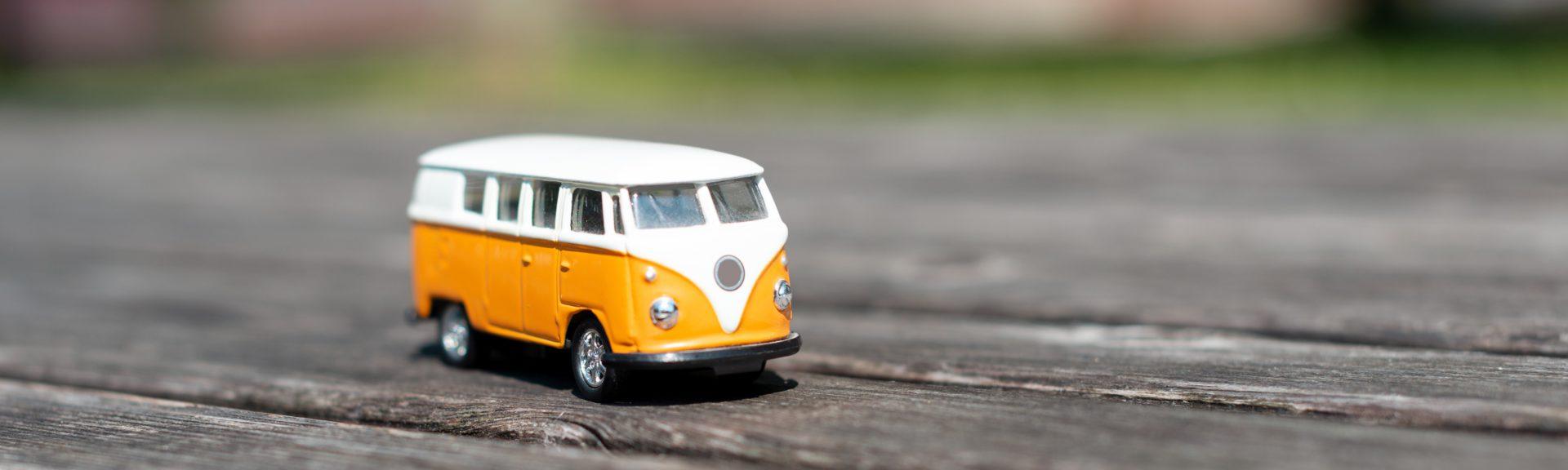 Auf einem Holzboden im Freien steht ein alter VW-Bus mit oranger Lackierung und weißem Dach.