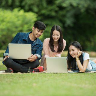 Studenten sitzen mit Laptops auf einer Wiese im Park