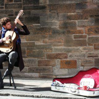 Ein Straßenmusiker sitzt mit seiner Gitarre vor einem Haus, neben ihm ein offener Gitarrenkoffer