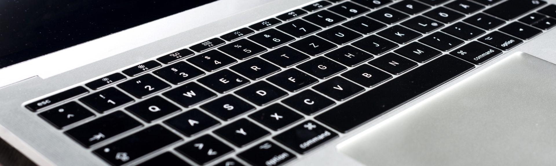 Schräge Ansicht einer Laptop-Tastatur mit schwarzen Tasten und Gehäuse aus Aluminium.