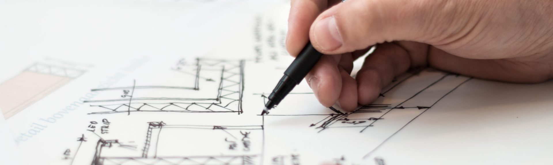 Nahaufnahme der Hände. Ein Architekt zeichnet einen Grundriss.