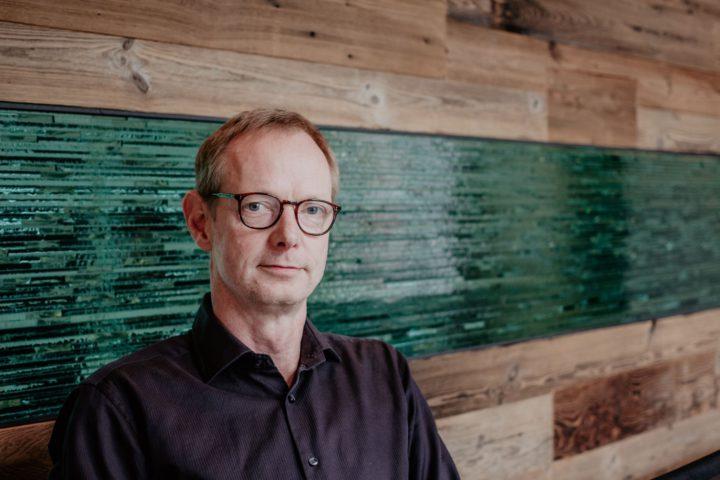 Portrait von Jan Schulz. Er sitzt in seimen Büro vor einer Wand aus Holz und Glas. Herr Schulz ist groß und schlank, trägt ein dunkles Hemd und eine Brille.